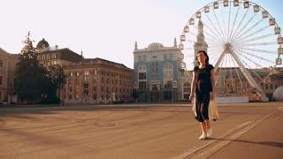 brunette lady enjoys morning walk in a big city. she wears black t-shirt and skirt.