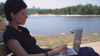 Brunette using laptop outdoors. Adult woman resting near lake in summer season typing on computer. Young businesswoman working or chatting or messaging in social net on the beach. Female with short