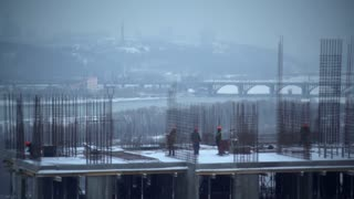 builders working outdoors in winter season. Workers build apartment house. group of people wearing in helmet. Men talking and do some work on the floor white snow. Urban city view with bridge river