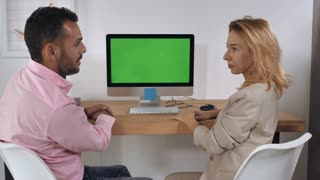 Business negotiation in office. Handsome professional man giving presentation showing on computer with green display. Caucasian blonde adult woman looking on screen pc listens attentively and showing