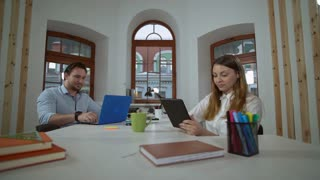 business partners sitting at the working place smiling. Caucasian woman using digital tablet wearing casual white blouse. Adult man with beard typing on computer in room with contemporary interior and