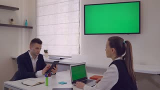 Business people looking on monitor with green screen and clap their hands. Coworkers in modern office using digital device for working