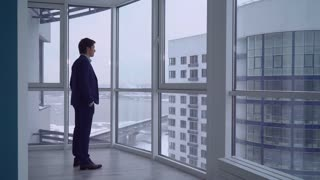 businessman in empty room with big panoramic windows looking on the urban city view. young professional man wearing in elegant suit alone in modern apartment. caucasian male deep in thought