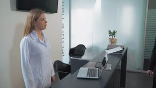 Businessman talking with nurse or receptionist in hospital. Happy smiling woman gesture patient in clinic