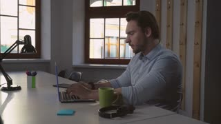 Businessman working at home. Adult man sitting at the desk with laptop. Focused entrepreneur looking on display try to solve the problem with new product or deal