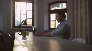 Businessman working in the office in sunny day. Handsome adult man typing on computer in office. Concentrated male sitting at the big wooden table looking screen laptop