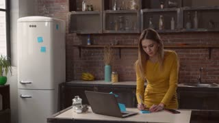 businesswoman writing notes in kitchen. Adult woman working at home on the cooking table laptop. Caucasian lady wearing in elegant dress glues blue sticky notes on fridge in apartmen