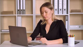 busy business woman shopping online sitting at the desk in modern office. attractive worker with blonde hair using internet make payment. adult female wearing black hair