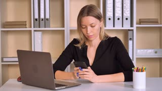 caucasian adult employer sitting at the workplace using smartphone. attractive business woman sitting at the desk in modern office messaging on mobile or using app for chatting online