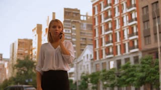 caucasian blonde talking by mobile in town professional business worker standing on the street urban city landscape. successful woman wearing white shirt and black skirt. slow motion