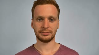 caucasian guy with red hair showing emotion terrible noise. handsome redheaded men wearing in casual t-shirt. Portrait ginger young caucasian man on grey background