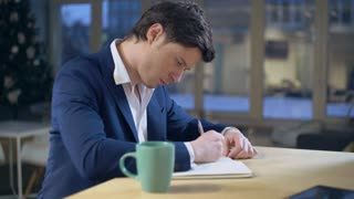 Caucasian male hand writing notes in notebook. Handsome man sitting at the wooden desk colored cup with desk. young businessman planned to do list