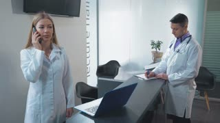 Caucasian nurse or doctor s assistant using telephone has phone conversation with patient. Adult doctor standing near reception desk fill documents in clinic