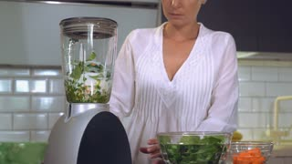 Caucasian woman making green healthy smoothie in the kitchen. Female wearing in white sleepwear using blender mixing vegetables at home