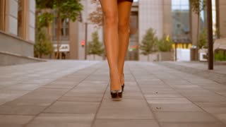 caucasian young businesswoman wearing formal elegant clothes and high-heels shoes walking in city center. on the background modern office building. slow motion