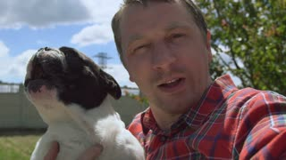 caucasian young man holding dog and take selfie portrait. Male having fun looking at the camera with french bulldog laughing and talking. Guy with pet outdoors in sunny day slow motion