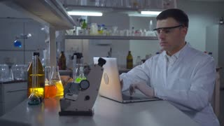 Chemist Engineer working with laptop in laboratory. Adult man wearing in lab coat typing on computer. Caucasian professional entering data focused at work in the evening