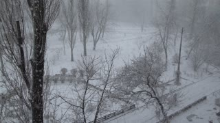 city in snowing day winter season. snowfall in town. People hurry home or on business wearing in jackets with hood