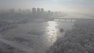 City in the snow, flying over the forest and the river, the bridge can be seen in the distance and the sunrise. Aeria video 4k