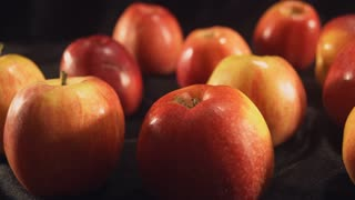 Close up colored apples on one back red on another yellow