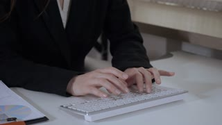 close up details businesswoman typing on white keyboard. unrecognizable woman entering data on computer