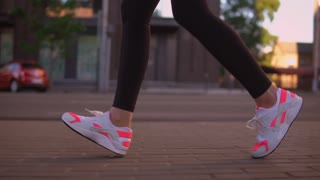 close up details legs sport outdoor. unrecognizable woman running down the street. feet shod in sneakers bright colors white and pink