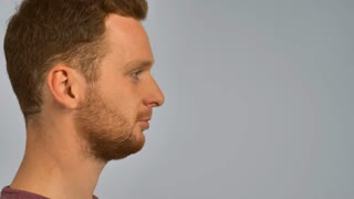 close up face in profile caucasian guy with red hair sneezing. handsome redhead men with beard. portrait young man on grey background has allergy or common cold