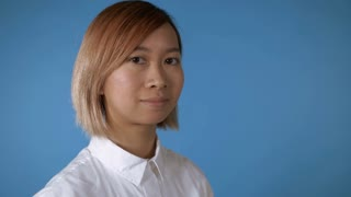close up face young asian businesswoman posing on blue background in studio. attractive korean woman with blond hair wearing white casual shirt looking at the camera