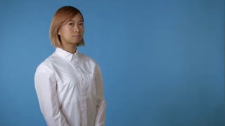close up face young asian businesswoman posing showing hand gesture listening you on blue background in studio. attractive korean woman with blond hair wearing white casual shirt looking at the camera