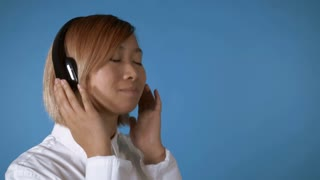 close up face young asian female dancing using headphones on blue background in studio. attractive korean woman with blond hair wearing white casual shirt looking at the camera with smile