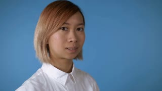 close up face young asian female posing on blue background in studio. attractive korean woman with blond hair wearing white casual shirt looking at the camera laughing