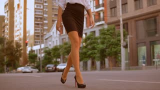 Close up female legs walking along the sidewalk. unrecognizable business woman wearing black skirt and high-heeled shoes. on the background urban city landscape. slow motion