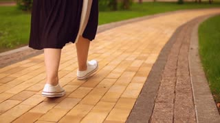 close up of female legs wearing white sneakers and black dress. sporty and active lady walks in the park.