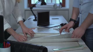Close up people working with blueprint in the office. On the desk laptop. Woman and man hands holding architectural plan
