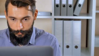 close up portrait bearded man working with computer in office. handsome man focused at screen laptop than looking at the camera