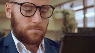 close up portrait handsome man with beard using touch screen digital tablet. businessman scrolling reading news or shoping online