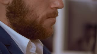 close up unrecognizable man touching his red beard. details redhead male