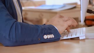 closeup details man wearing casual informal blue jacket typing on white keyboard. unrecognizable person sitting at the wooden desk working on computer