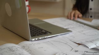 Closeup woman architect working with architectural plan. On working place laptop