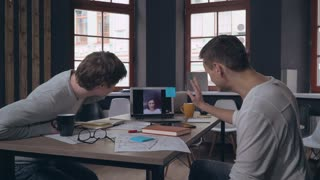 Coworkers have video call conference with friend. Two men sitting in the office have funny conversation with woman. Designers looking on screen laptop using application for calling