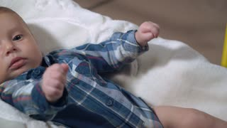 Cute boy wearing shirt lying on white blanket. Child three month old. Serious and attentive kid