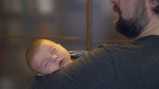 dad holding sleeping baby and singing song. caucasian child falls asleep in father s arms. newborn wearing in shirt