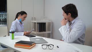 dentist discussing with adult colleague x-ray scans. Two young professional doctors talking in office in clinic