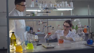Diverse team working in laboratory. Professional biologist observed results and discussing with colleague. Young woman student explain teacher technology carrying out experiments