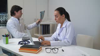 Doctor holding x-ray dictates diagnosis and conclusion for medical records. Woman nurse or assistant typing on computer. Colleagues sitting at the working place in clinic