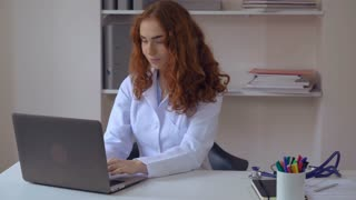 doctor or assistant or nurse with curly red hair sitting at the working place typing on computer looking at the camera with happy friendly smile. Redhead woman wearing white lab coat on the desk