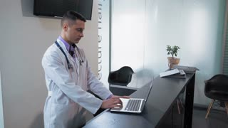Doctor s assistant greeting businesswoman in clinic. Man wearing in white coat using computer checking therapist schedule and looking free time for visit. Blonde woman talking with doctor in hospital