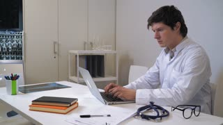 Doctor working on computer. Man wearing white coat focused looking on screen pc. On the desk x-ray phonendoscope and eyeglasses