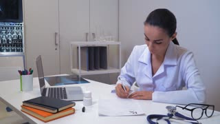 Doctor young professional woman writing prescription and giving to patient. Mixed race therapist sitting at the desk in office. Female working in hospital