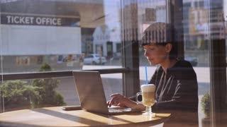 Elegant professional businesswoman using internet for working with document in cafe. Busy adult caucasian woman has coffee break in coffeehouse typing on computer in daytime